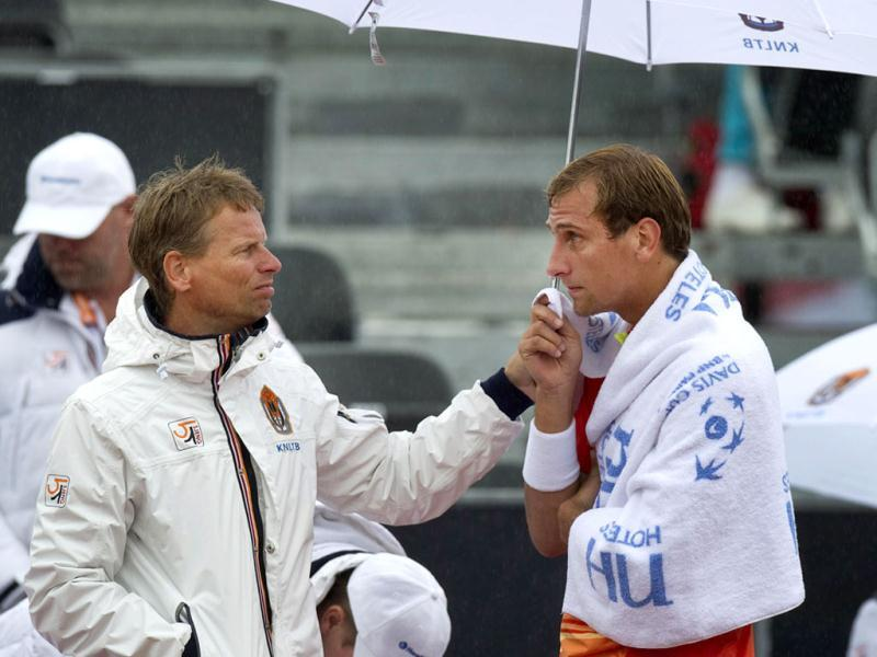 Team coach Jan Siemerink (L) of the Netherlands holds an umbrella for team player Thiemo de Bakker during a rain break in his Davis Cup tennis match against Roger Federer of Switzerland in Amsterdam September 14, 2012. Reuters