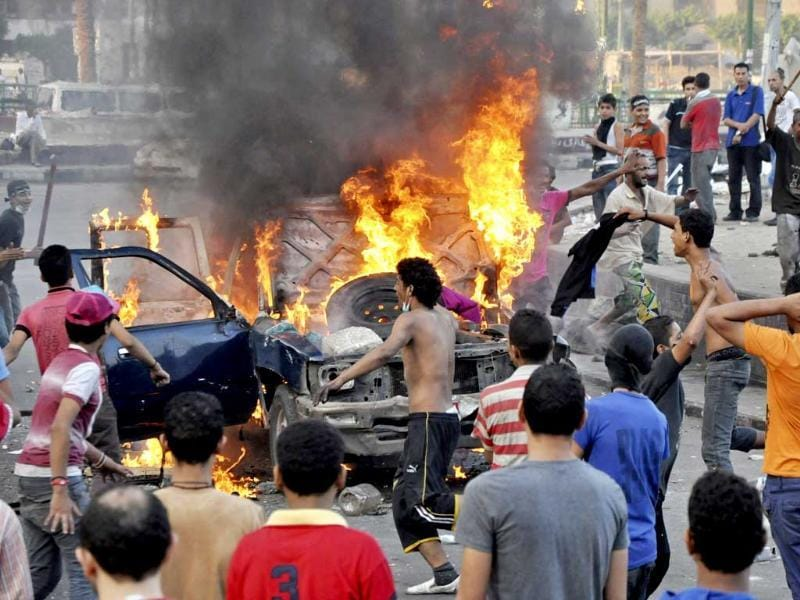 Egyptian protesters gather around a burning vehicle in downtown Cairo, Egypt. AP