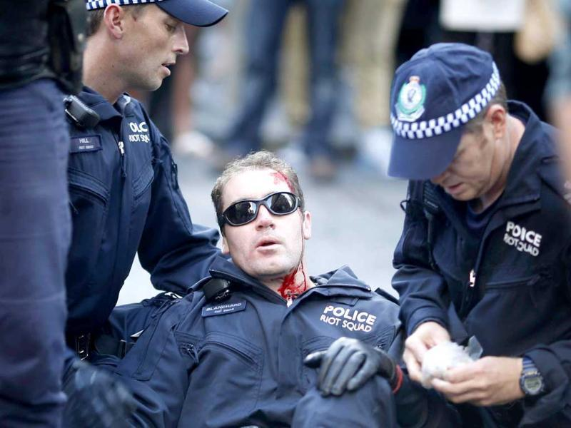 A policeman, injured by protesters, is assisted by colleagues in central Sydney. Reuters/Tim Wimborne