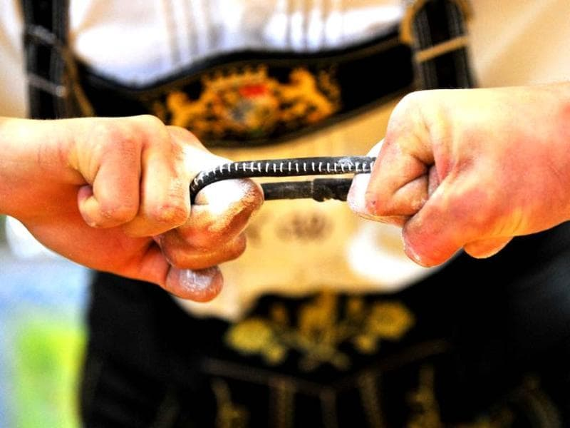 Finger wrestlers compete in the German Finger Wrestling Championship in Warngau, southern Germany. More than 150 men taking part in the traditional Bavarian event try to pull their opponent over the table by using their fingers and a rubber strap only. (AFP photo/ Frank Leonhardt)