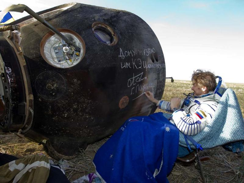 International Space Station (ISS) crew member Russian cosmonaut Gennady Padalka signs an autograph on the Soyuz capsule after landing near the town of Arkalyk in northern Kazakhstan. AP photo