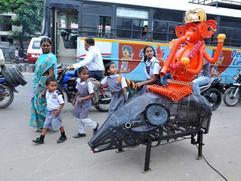 Bystanders looks at an idol of Lord Ganesha sitting on mechanised moving mouse made by designer Sudhakar Yadav in Hyderabad. Yadav designed 6.6 foot tall Ganesha idol sitting on a mechanised moving mouse made with old automobile parts for the ten-day long Ganesh festival. AFP/Noah Seelam