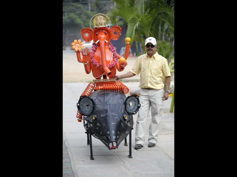 Designer Sudhakar Yadav stands next his idol of Lord Ganesha sitting on a mechanised moving mouse in Hyderabad. Yadav designed 6.6 foot tall Ganesha idol sitting on a mechanised moving mouse made with old automobile parts for the ten-day long Ganesh festival. AFP/Noah Seelam