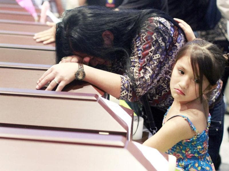 A girl comforts her mother crying on a coffin containing the remains of her relative during a ceremony in Medellin. The prosecutor's office on Tuesday delivered the 17 sets of remains to the families of civilians who were killed two years ago by paramilitary and rebel fighters during the Colombian armed conflict, officials said. Reuters Photo