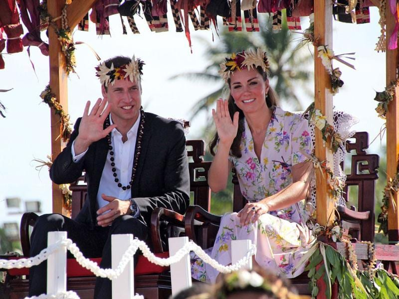 Britain's Prince William and his wife Catherine, the Duchess of Cambridge, wave as they sit on a platform while being carried to the plane for his farewell with wife Catherine from Tuvalu in Funafuti. AFP Photo