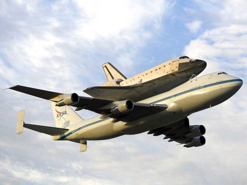 Space shuttle Endeavour, bolted atop a modified jumbo jet, makes its departure from the Kennedy Space Center in Cape Canaveral, Florida. (AP/Terry Renna)