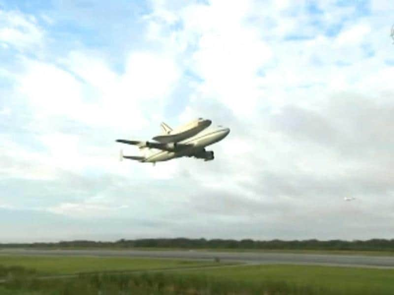 This image by NASA TV shows space shuttle Endeavour atop NASA's Shuttle Carrier Aircraft doing a low level flyby at the Shuttle Landing Facility in the early morning hours at NASA's Kennedy Space Center in Cape Canaveral, Florida. (AP/NASA-TV)