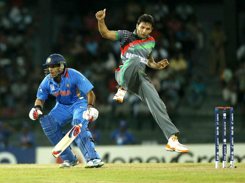 Yuvraj Singh, left, tries to run between wickets as Afghanistan's bowler Gulbodin Naib jumps during their ICC Twenty20 Cricket World Cup match in Colombo, Sri Lanka. AP/Eranga Jayawardena