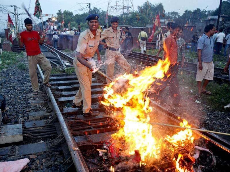 Bandh: Policemen remove a burning effigy representing the government during a protest in Allahabad. AP/Rajesh Kumar Singh