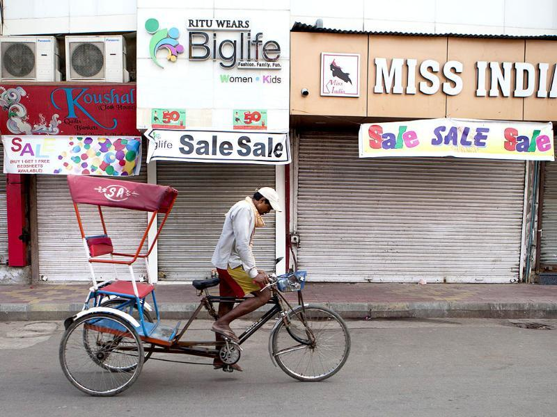 Bandh: A rickshaw driver pedals past closed shops as he looks for passengers at Lajpat Nagar market in New Delhi. AFP/Andrew Caballero-Reynolds