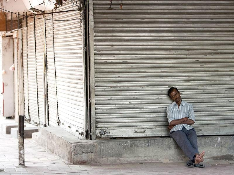 A resident sleeps in front of closed shops at Lajpat Nagar market in New Delhi. Opposition parties and trade unions called for shopkeepers, traders and labourers in India to block railway lines and close markets to protest against reforms, designed by Manmohan Singh. AFP/Andrew Caballero-Reynolds