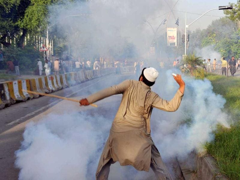 A Pakistani Muslim protester throws a tear gas shell back towards police as demonstrators attempt to reach the US embassy during a protest against an anti-Islam film in Islamabad. AFP/Aamir Qureshi