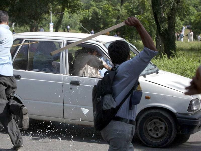 Protesters use sticks to smash the windscreen and windows of a car during an anti-America protest march in Islamabad. Reuters