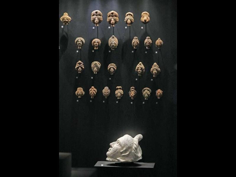 A 2nd century Egyptian woman mask, bottom, and several 3rd century heads of women, top, are displayed at the Louvre museum in Paris. The Louvre museum is unveiling its new wing and galleries dedicated to the arts of Islam, and new dragon-fly shaped building marking the museum's greatest development since the iconic glass pyramid constructed twenty years ago. (AP Photo/Remy de la Mauviniere)