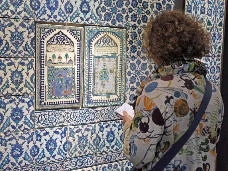 A member of the media examines a ceramic tile wall displayed at the Louvre museum in Paris. The Louvre museum is unveiling its new wing and galleries dedicated to the arts of Islam, and new dragon-fly shaped building marking the museum's greatest development since the iconic glass pyramid constructed twenty years ago.(AP Photo/Remy de la Mauviniere)