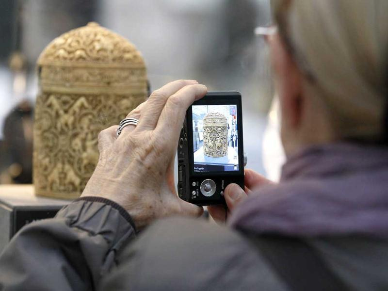 A member of the media takes a snapshot of a 4th century Ivory box made for the youngest son of the caliph Abd al-RahmanIII, displayed at the Louvre museum in Paris. The Louvre museum is unveiling its new wing and galleries dedicated to the arts of Islam, and new dragon-fly shaped building marking the museum's greatest development since the iconic glass pyramid constructed twenty years ago. (AP Photo/Remy de la Mauviniere)