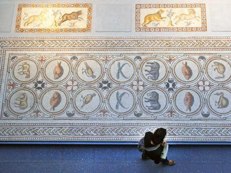 A member of the media walks past mosaics displayed, displayed at the Louvre museum in Paris. The Louvre museum is unveiling its new wing and galleries dedicated to the arts of Islam, and new dragon-fly shaped building marking the museum's greatest development since the iconic glass pyramid constructed twenty years ago. (AP Photo/Remy de la Mauviniere)