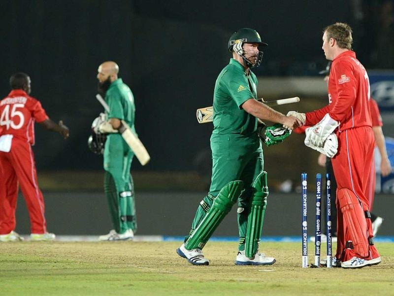 Zimbabwean cricket captain Brendan Taylor (R) congratulates South African cricketer Richard Levi (C) after South Africa won the ICC Twenty20 Cricket World Cup match between South Africa and Zimbabwe in Hambantota. AFP photo