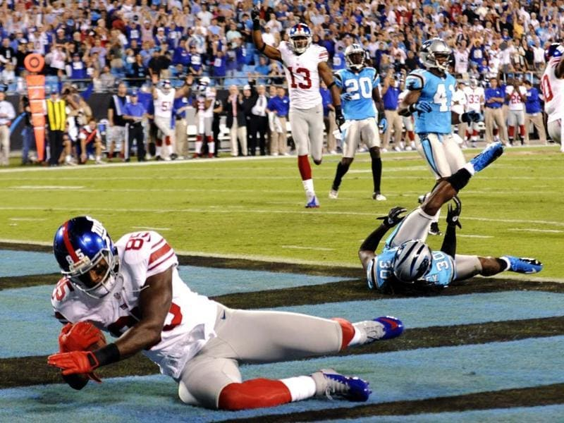 New York Giants wide receiver Martellus Bennett catches a touchdown pass past Carolina Panthers safety Charles Godfrey during the first quarter of an NFL football game in Charlotte, NC. AP/Mike McCarn