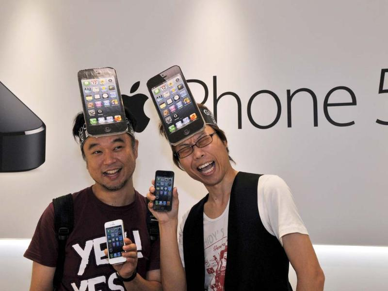 Customers react after purchasing Apple's new iPhone 5 smartphone at the Softbank mobile phone shop in Tokyo. AFP/Yoshikazu Tsuno