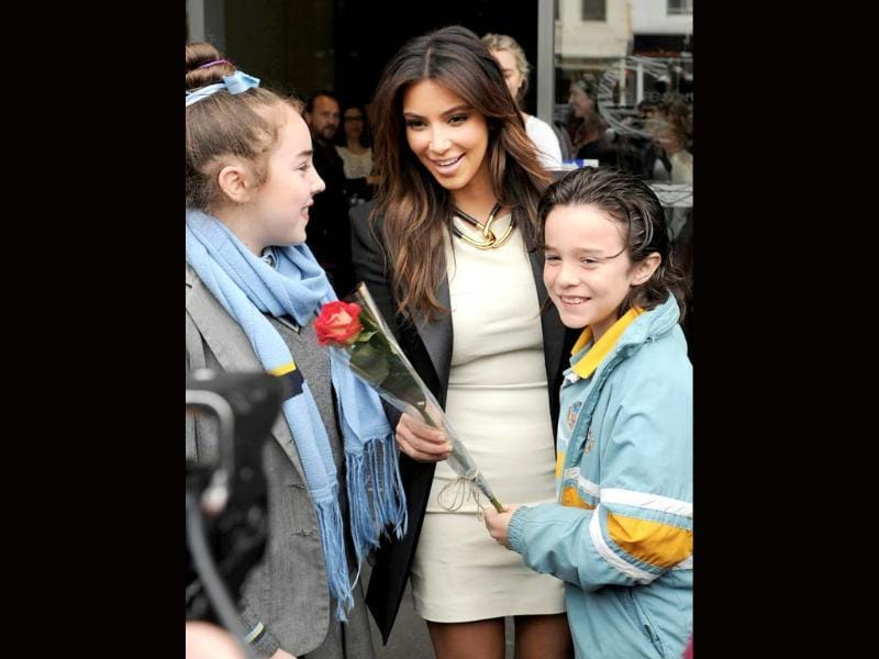 Kim Kardashian receives a flower from a 10-year-old boy Conrad Noonan-Barros as his sister Helena, 13, watches outside a radio station in Melbourne, Australia. AP/Mal Fairclough