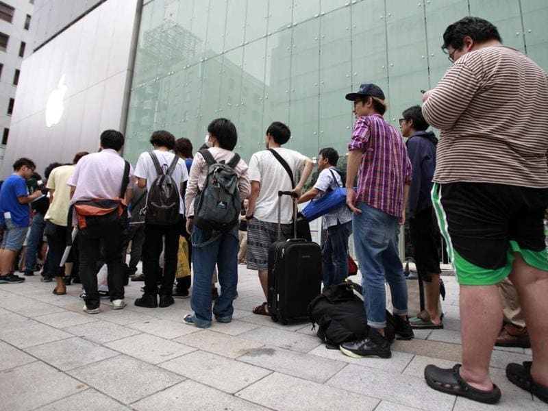 People wait in line outside an Apple store to purchase Apple Inc's iPhone 5 in Tokyo's Ginza district. Apple Inc's iPhone 5 hit stores around the globe with fans snapping up the device that is expected to fuel a huge holiday quarter for the consumer giant. Reuters/Yuriko Nakao