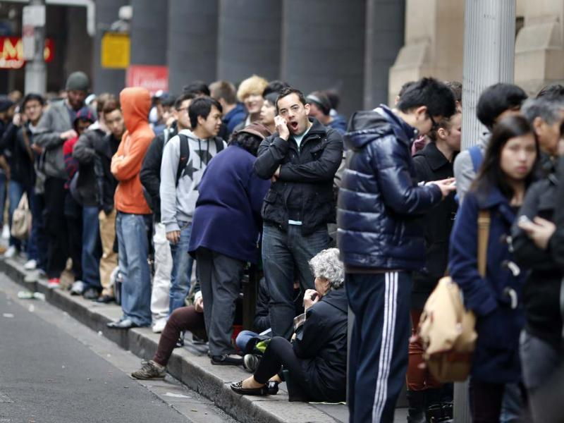People queue outside an Apple store as they wait to buy an iPhone 5, in central Sydney. Apple Inc's iPhone 5 hit stores around the globe with fans snapping up the device that is expected to fuel a huge holiday quarter for the consumer giant. Reuters/Tim Wimborne