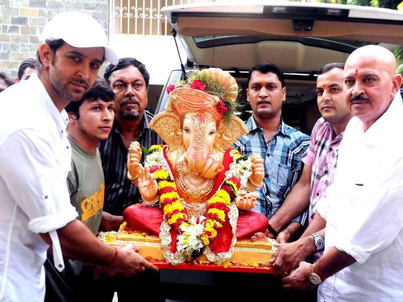 Hritik Roshan and Rakesh Roshan carry Lord Ganesh idol to immerse in water for blessings during Ganesh Chaturthi in Mumbai on September 20. (AFP Photo)