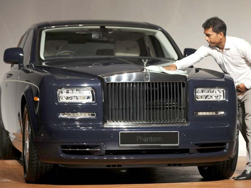 A staff member cleans a Rolls Royce Phantom Series II car as it is unveiled to the media at an event in Mumbai. AFP Photo