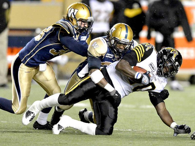 Hamilton Tiger-Cats' Brandon Rutley is tackled by Winnipeg Blue Bombers' Dan West and Will Ford during the second half of their CFL football game in Winnipeg. Reuters/Fred Greenslade