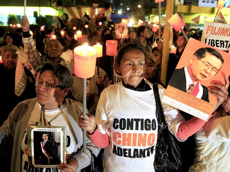 Supporters hold candles while holding images of former President Alberto Fujimori during a vigil for his recovery outside San Felipe Clinic in Lima. The shirt reads: