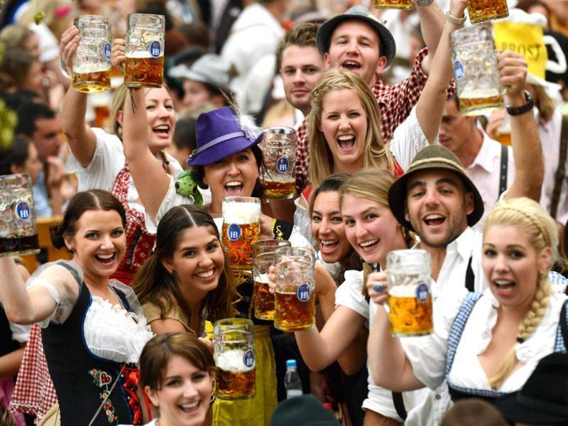 Visitors wearing traditional Bavarian clothes raise their beers in a festival tent at the start of the Oktoberfest beer festival at the Theresienwiese in Munich, southern Germany. AFP PHOTO / CHRISTOF STACHE