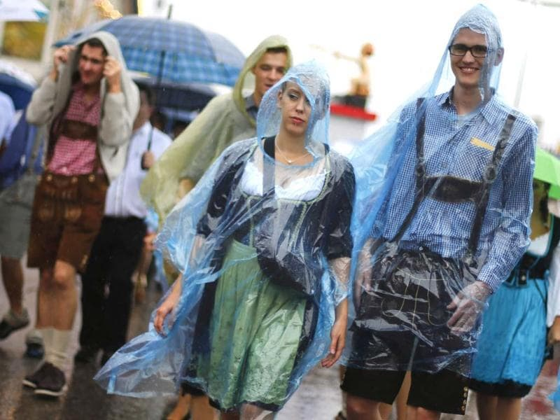 Revellers cover themselves from heavy rain as they stroll over the Munich Oktoberfest at the Theresienwiese in Munich. REUTERS/Kai Pfaffenbach