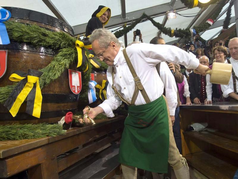Mayor of Munich Christian Ude taps the first beer barrel during the official opening of the famous Bavarian