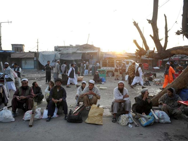 Day laborers sit on the curb of a street in downtown Kabul as they wait to be picked up and employed for the day. AFP/Roberto Schmidt