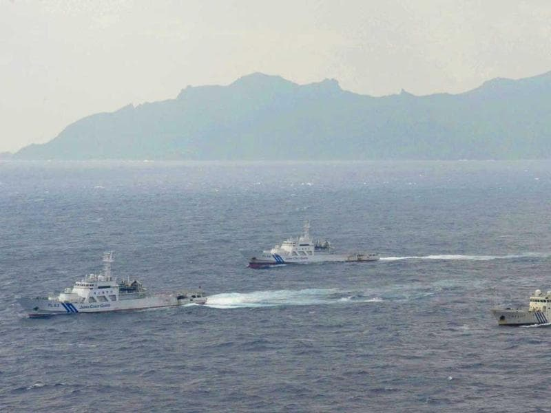 Japan Coast Guard vessels sail along with Chinese surveillance ship Haijian No. 66, near disputed islands called Senkaku in Japan and Diaoyu in China, seen in background, in the East China Sea. AP/Kyodo News