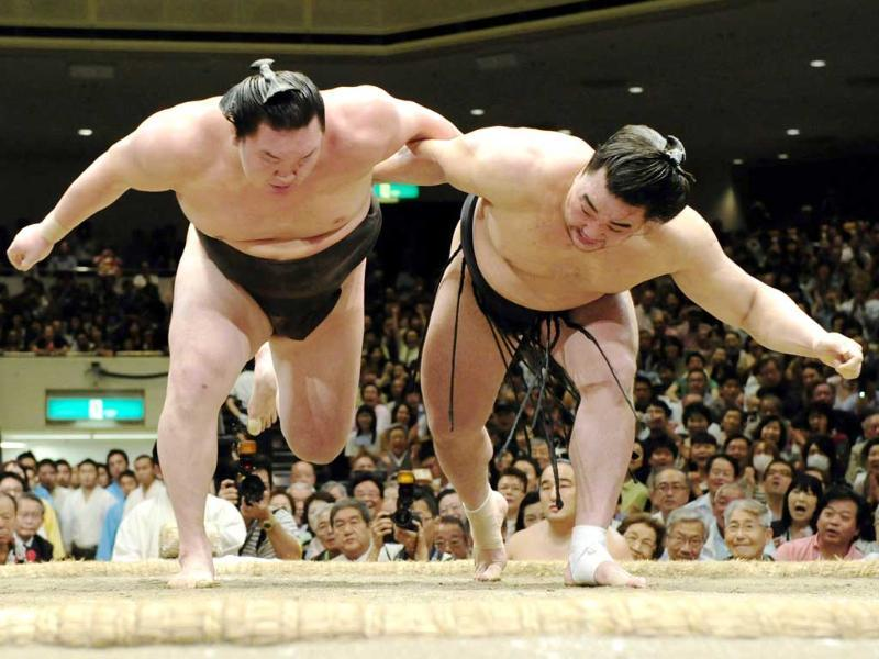 Mongolian sumo wrestler Harumafuji and compatriot and grand champion Hakuho fight during the Autumn Grand Sumo Tournament in Tokyo. Harumafuji won the tournament and moved a step closer to promotion to the sport's highest rank. AP/Kyodo News