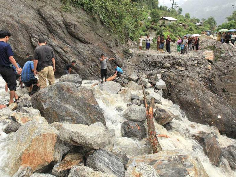 In this handout photograph received from the Sikkim Information and Public Relation Department (IPR) onlookers watch as rescue work following landslides caused by flash floods takes place on the Mongon – Chungthang road, some 30 kms north of the Gangtok. (AFP photo)