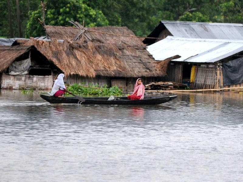 Villagers paddle their country boat near submerged houses in Kaziranga village, some 575 kms from Guwahati. (AFP photo/ Biju Boro)