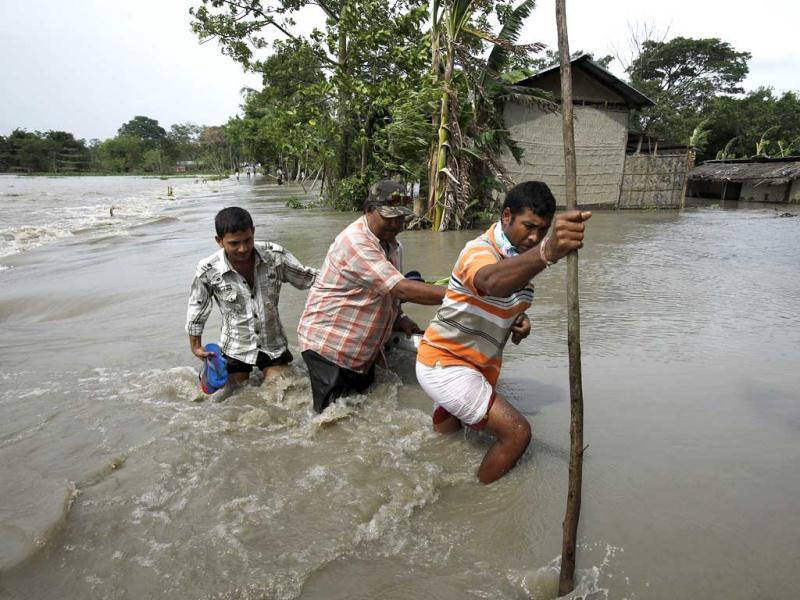 A man holds a child and steps from a banana raft in Lachi Bishnupur village, about 65 kilometers west of Guwahati. (AP Photo/Anupam Nath)