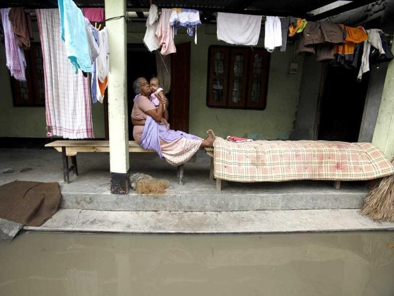 An elderly woman holds her grand daughter at home surrounded by floodwaters in Lachi Bishnupur village, about 65 kilometers west of Guwahati. (AP Photo/Anupam Nath)