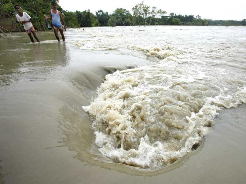 Villagers wade through floodwaters in Lachi Bishnupur village, about 65 kilometers west of Guwahati. (AP Photo/Anupam Nath)