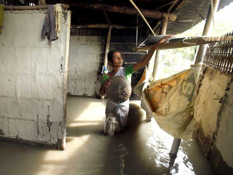 A woman removes a bamboo basket from her flooded house in Lachi Bishnupur village, about 65 kilometers west of Guwahati. (AP Photo/Anupam Nath)