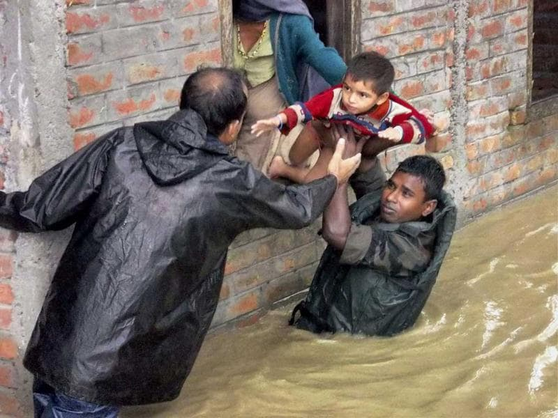 Army personnel shift flood-affected people to safer places at Dhola in Tinsukia district. (PTI Photo)