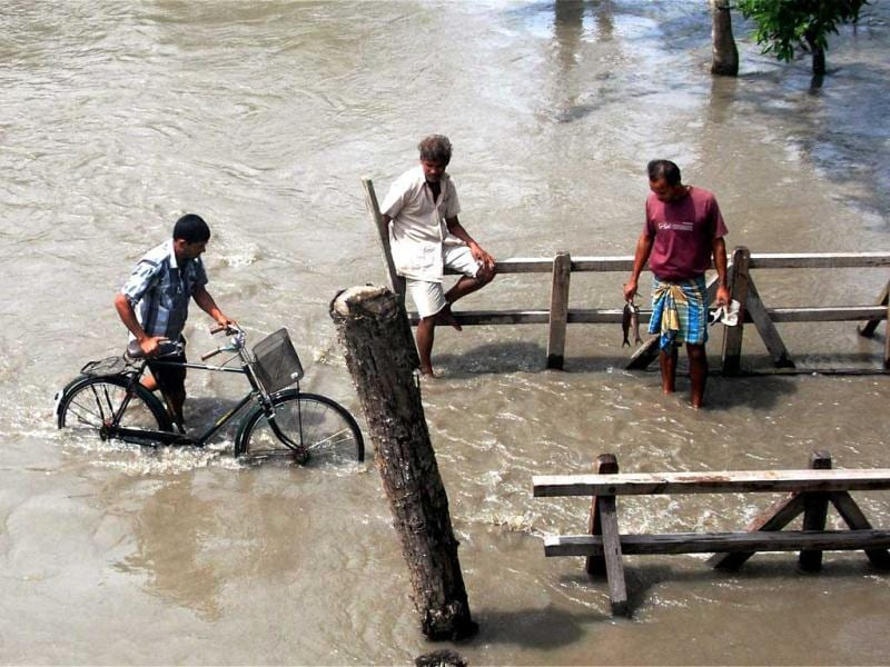 Villagers wade through the flood water at Kanikuch in Kamrup district in Assam. (PTI Photo)