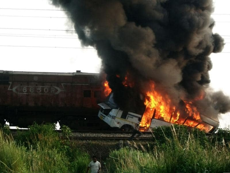 A college bus is seen on fire after a train rammed into it killing at least seven people in Bihar's Siwan district. HT