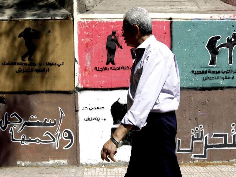A man walks past anti-sexual harassment graffiti along Mohamed Mahmoud Street near Tahrir Square in Cairo. The Arabic words read,