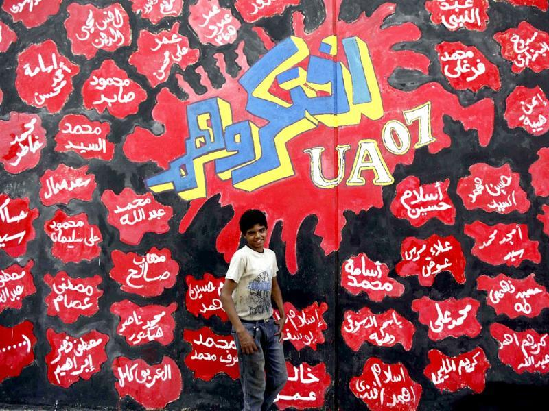 A boy walks past graffiti along Mohamed Mahmoud Street near Tahrir Square in Cairo. The Arabic words are names of 74 Ultras Al Ahli soccer fans who died in the Port Said stadium and