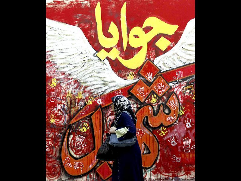 A woman walks past graffiti along Mohamed Mahmoud Street near Tahrir Square in Cairo. The graffiti on the walls of the street depicts some of the fiercest fighting that took place between protesters and security forces. The Arabic words read,