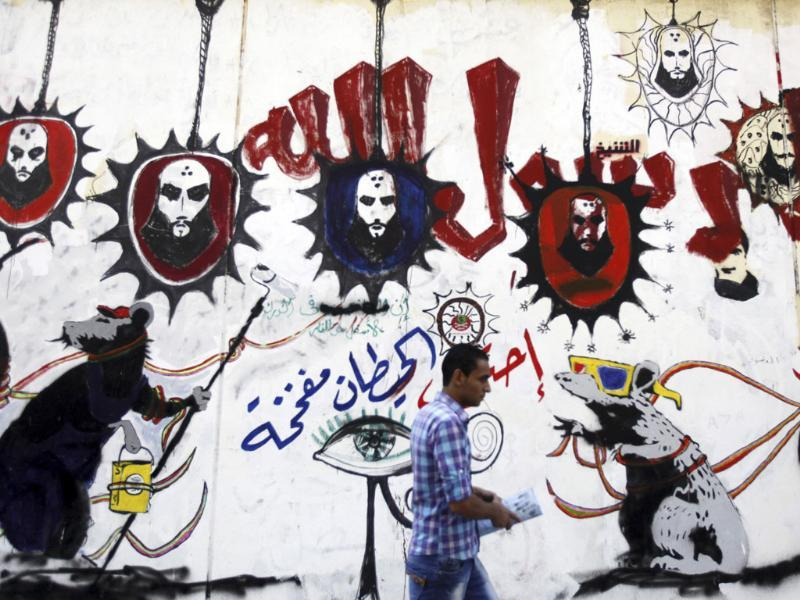 A man walks past graffiti in support of Prophet Muhammad along Mohamed Mahmoud Street near Tahrir Square in Cairo. The Arabic words read,